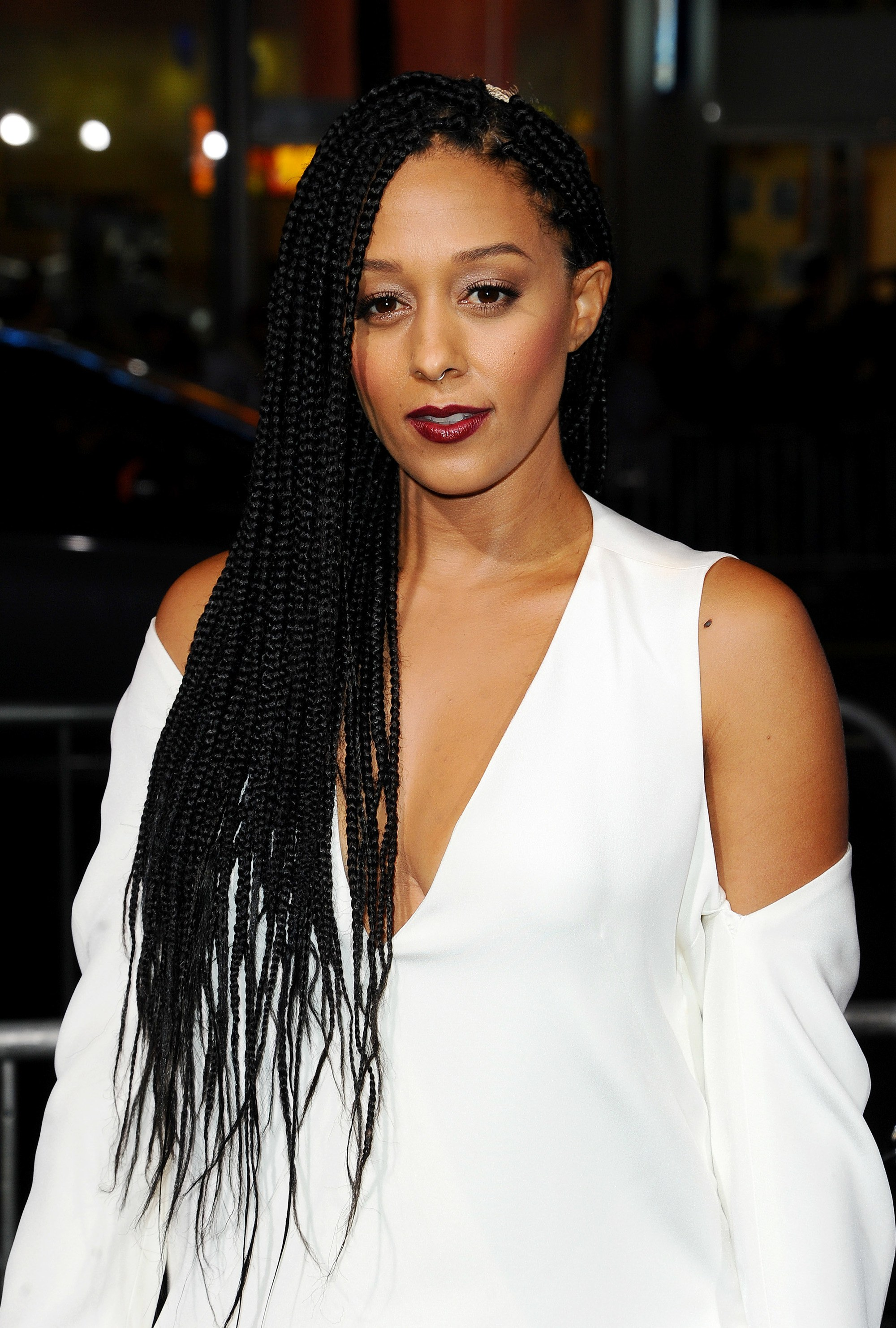 Tia Mowry with long box braids with loose sides, swept to the side on the horrible bosses red carpet