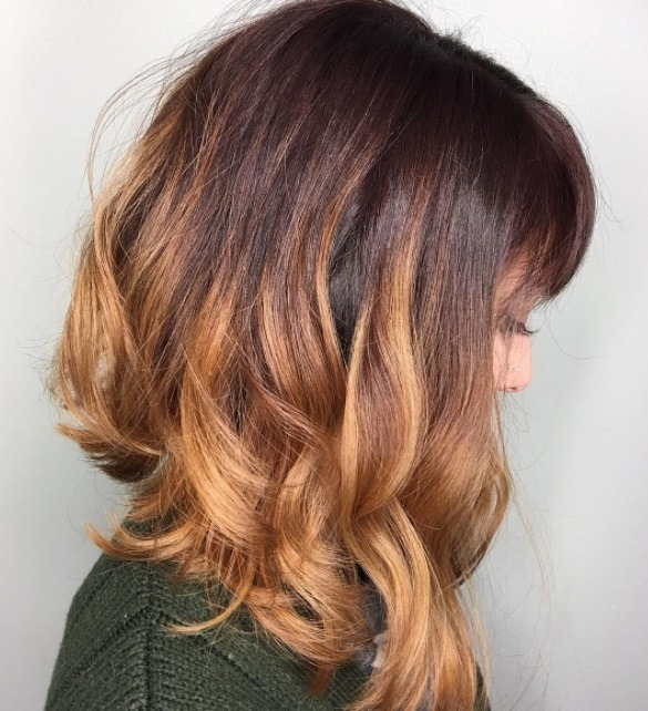 close up shot of woman with pumpkin ombre hair and long a line with bangs style at salon