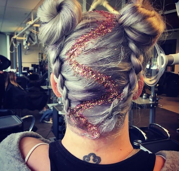 back view of a woman with silvery grey hair in upside down braided space buns with a zig zag glitter parting