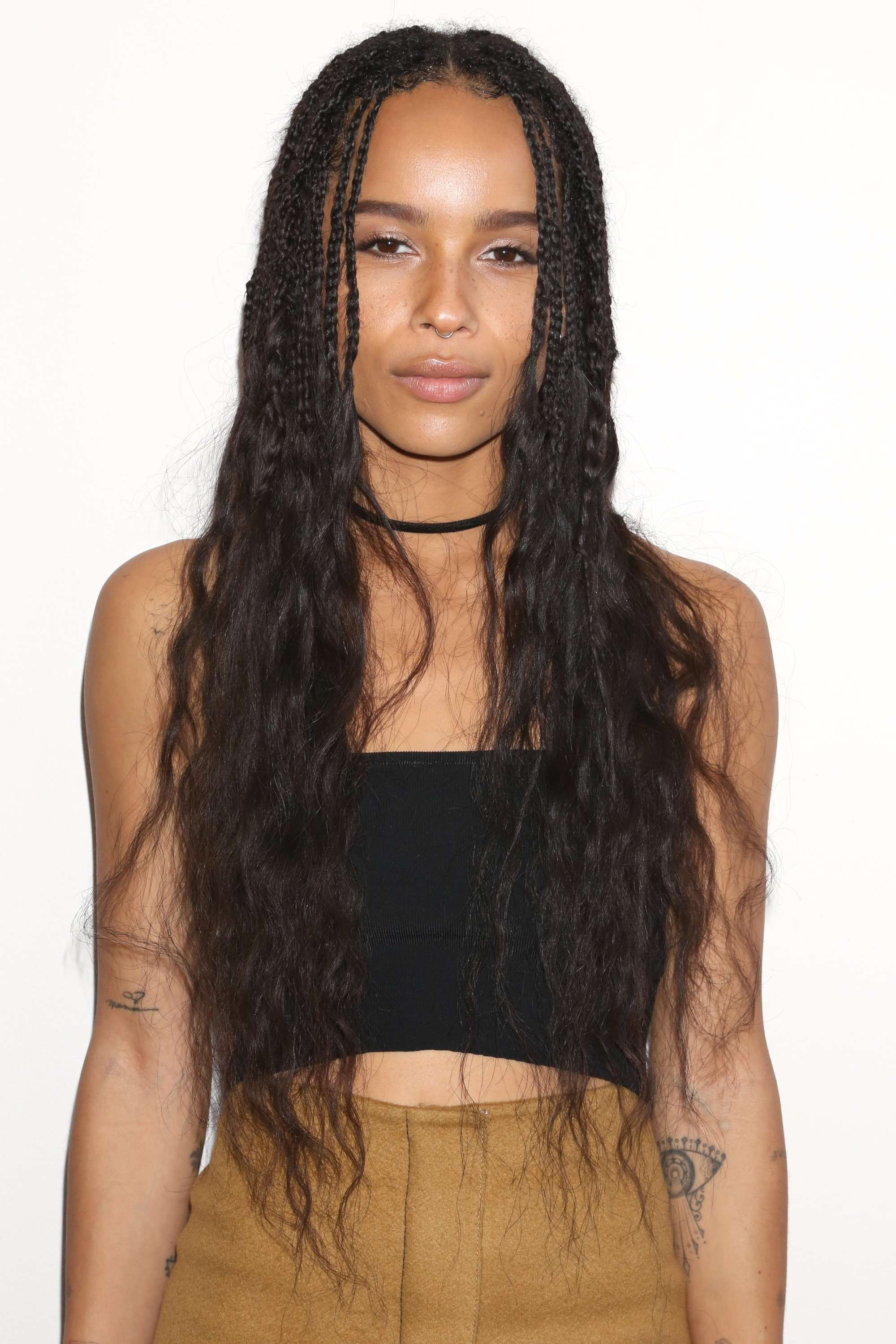 close up shot of zoe kravitz with curly box braids ends, wearing black crop top and mustard skirt