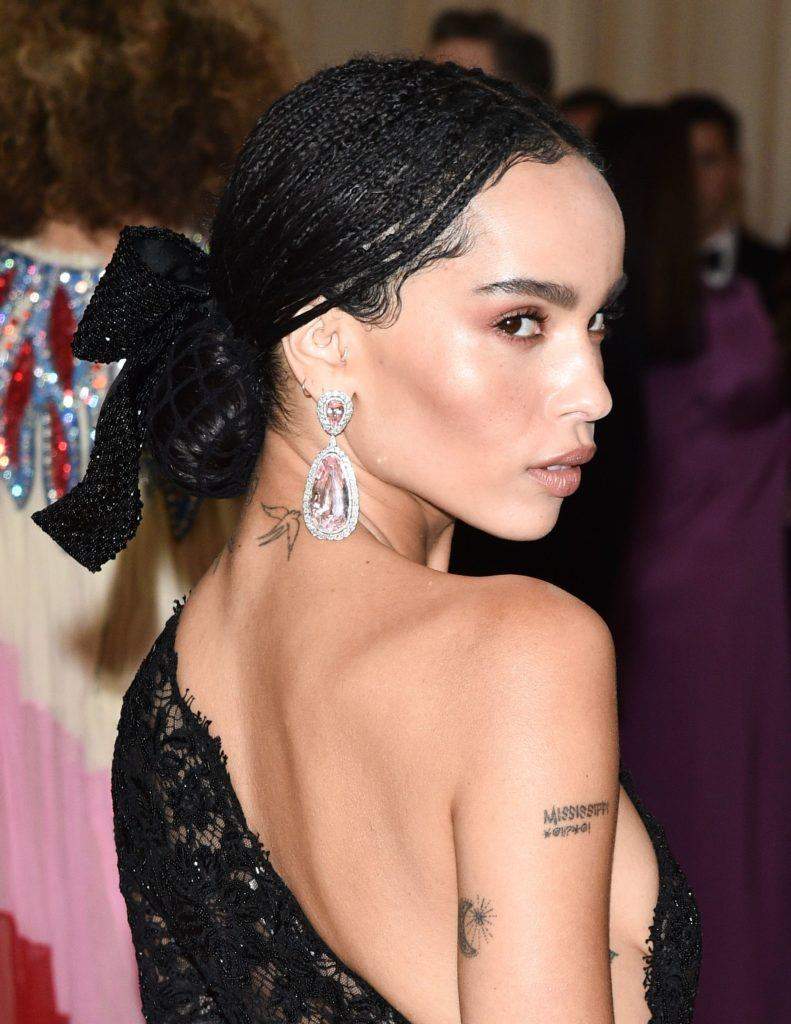 90s hairstyles: Zoë Kravitz dark brown micro braids in low bun with large black bow hair accessory on red carpet wearing one shoulder dress and large earrings