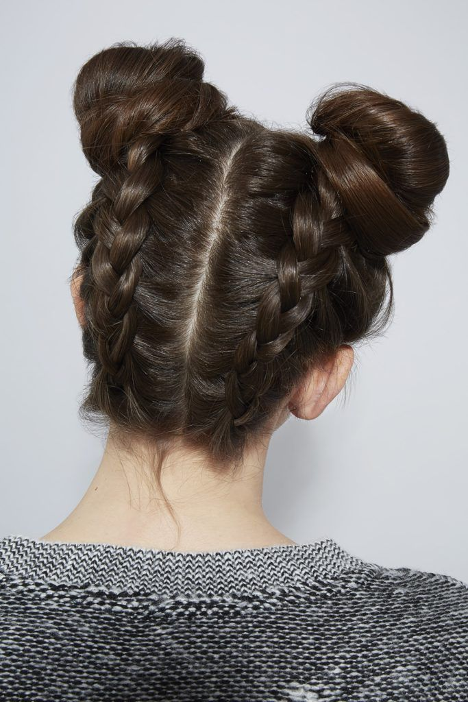 hair updos: back view of model with brown hair styled in braided space buns in studio