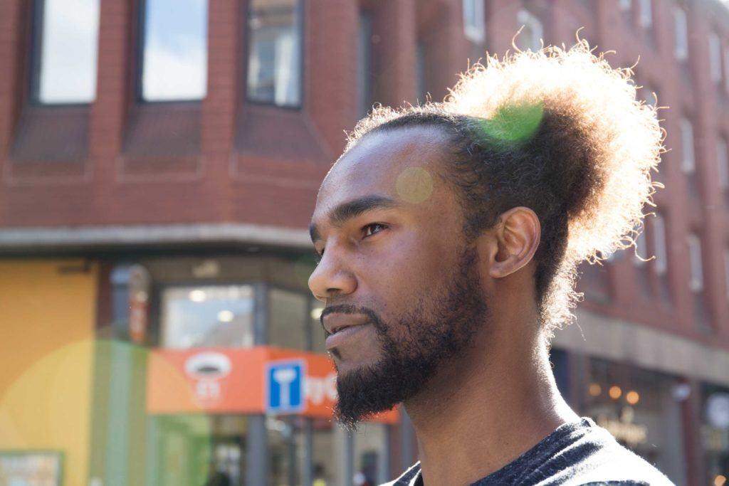 Man bun and beard: Close-up street style shot of a man with afro hair in a man bun with a beard