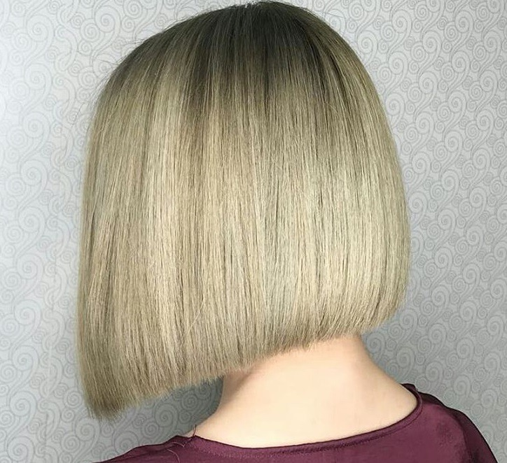 close up shot of woman with an ash blonde a line hair cut, wearing a red top and posing in a salon