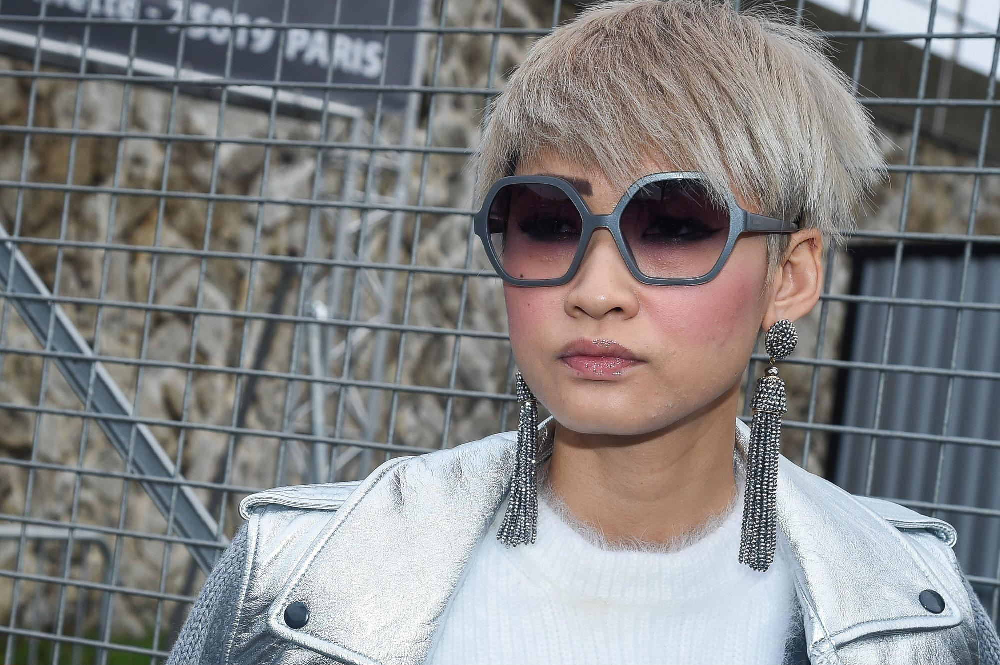street style shot of a woman with silver ash blonde choppy pixie haircut, wearing drop earrings and big sunglasses, with white top and jacket while posing on the street