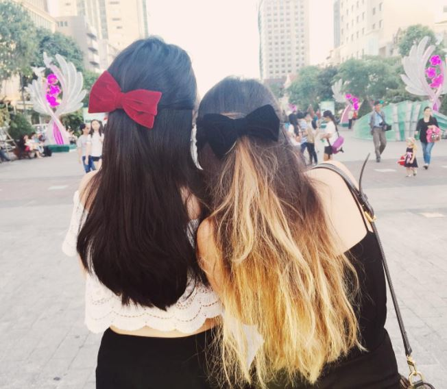 Two friends with dark brown and dark blonde ombre hair with half-up, half-down hairstyle with large velvet bows