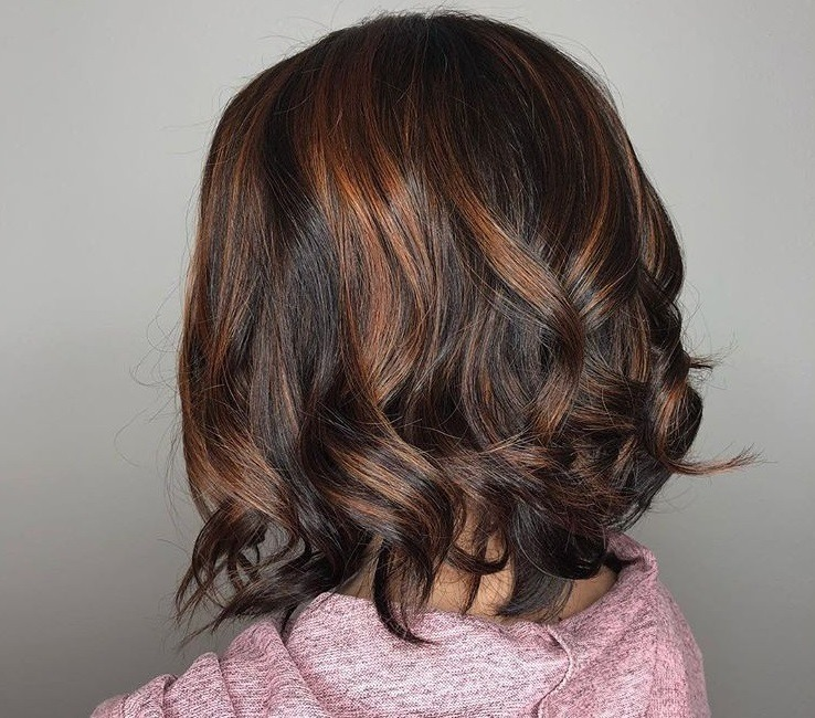 Cinnamon hair colour: Close up shot of a woman with a curly dark brown bob with cinnamon highlights.