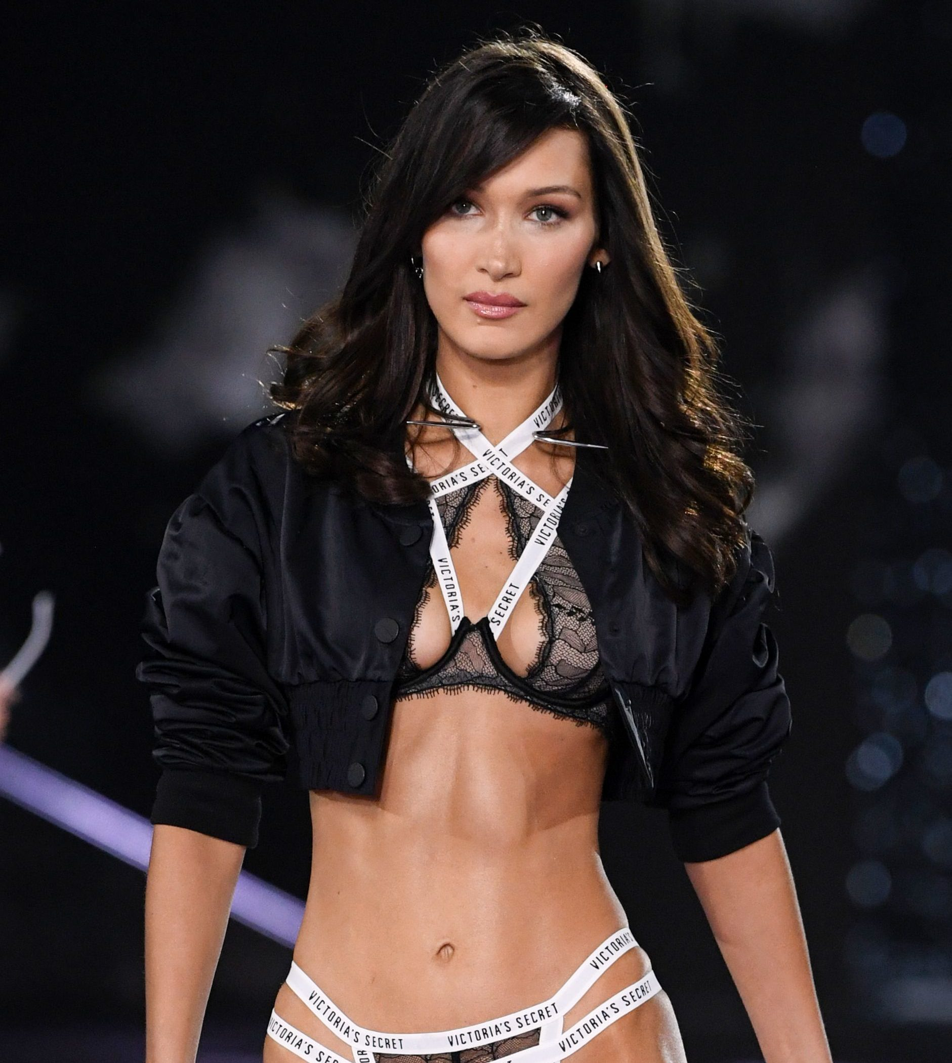 Victoria's Secret Fashion Show 2018: Bella Hadid with her chocolate brown medium-length hair styled into a curly blow out with a side-swept fringe, wearing a black jacket with lingerie on the runway