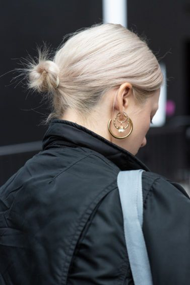 Woman with short bleached blonde hair styled into a low bun, wearing black jacket with hoop earrings on the street