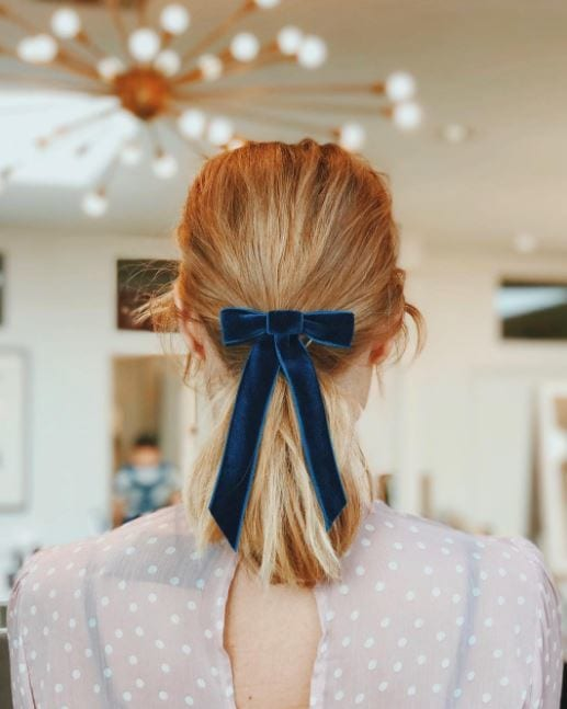 back view of medium length blonde hair with velvet bow ribbon