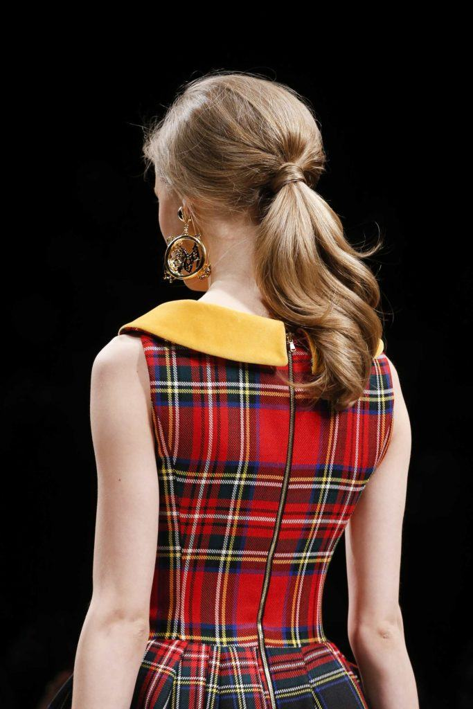back shot of model on the runway with sleek bouffant ponytail hairstyle, wearing checked dress and earrings