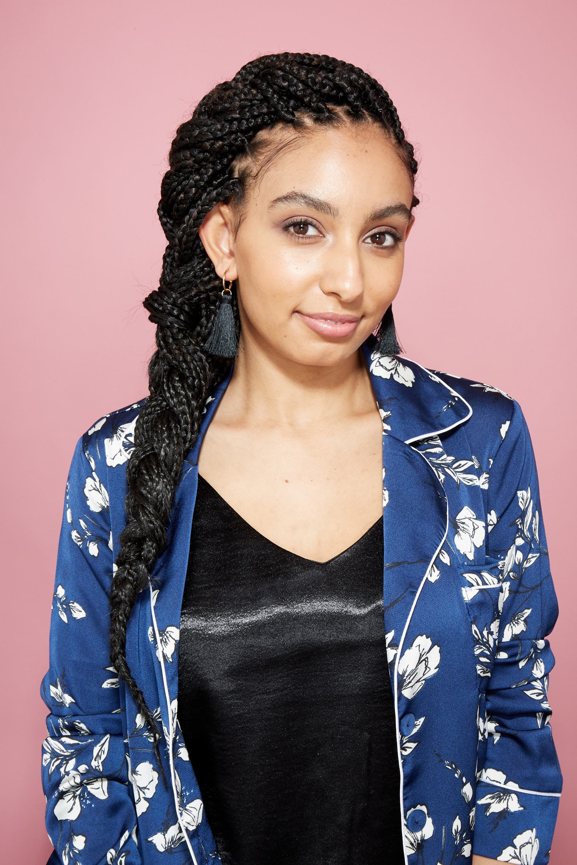 hair updos: woman with box braids styled in a side french braid in studio with pink background wearing a navy floral blazer and tassel earrings