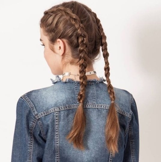 Easy hairstyles for fine hair: Brunette woman with long hair in double boxer braids wearing a denim jacket.