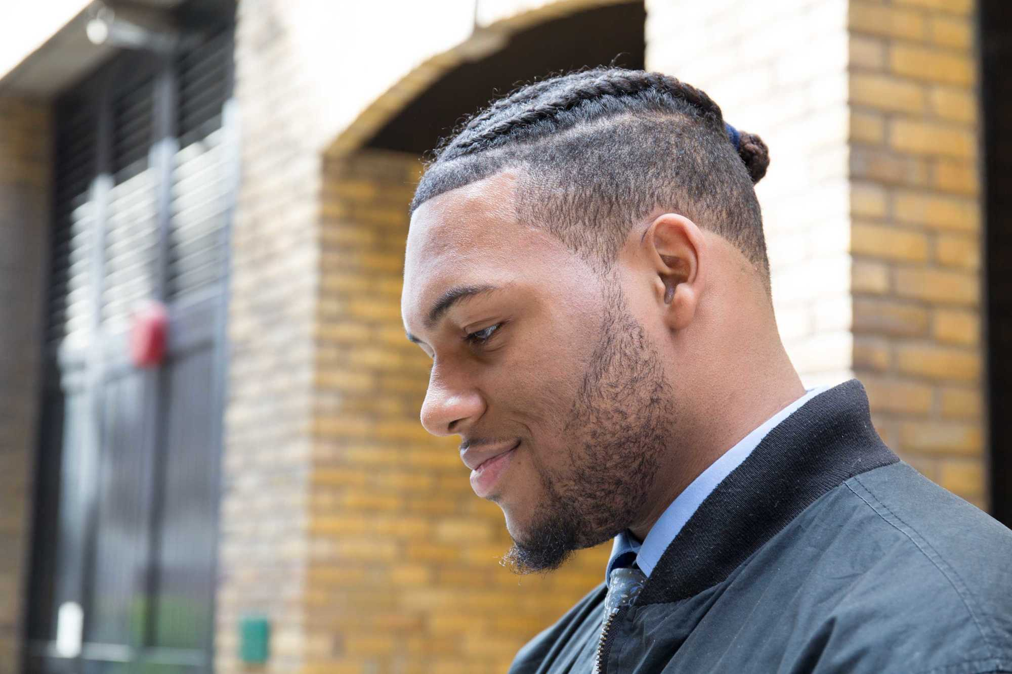 Man bun and beard: Close-up street style shot of a man with braided hair in a man bun with an undercut and face stubble