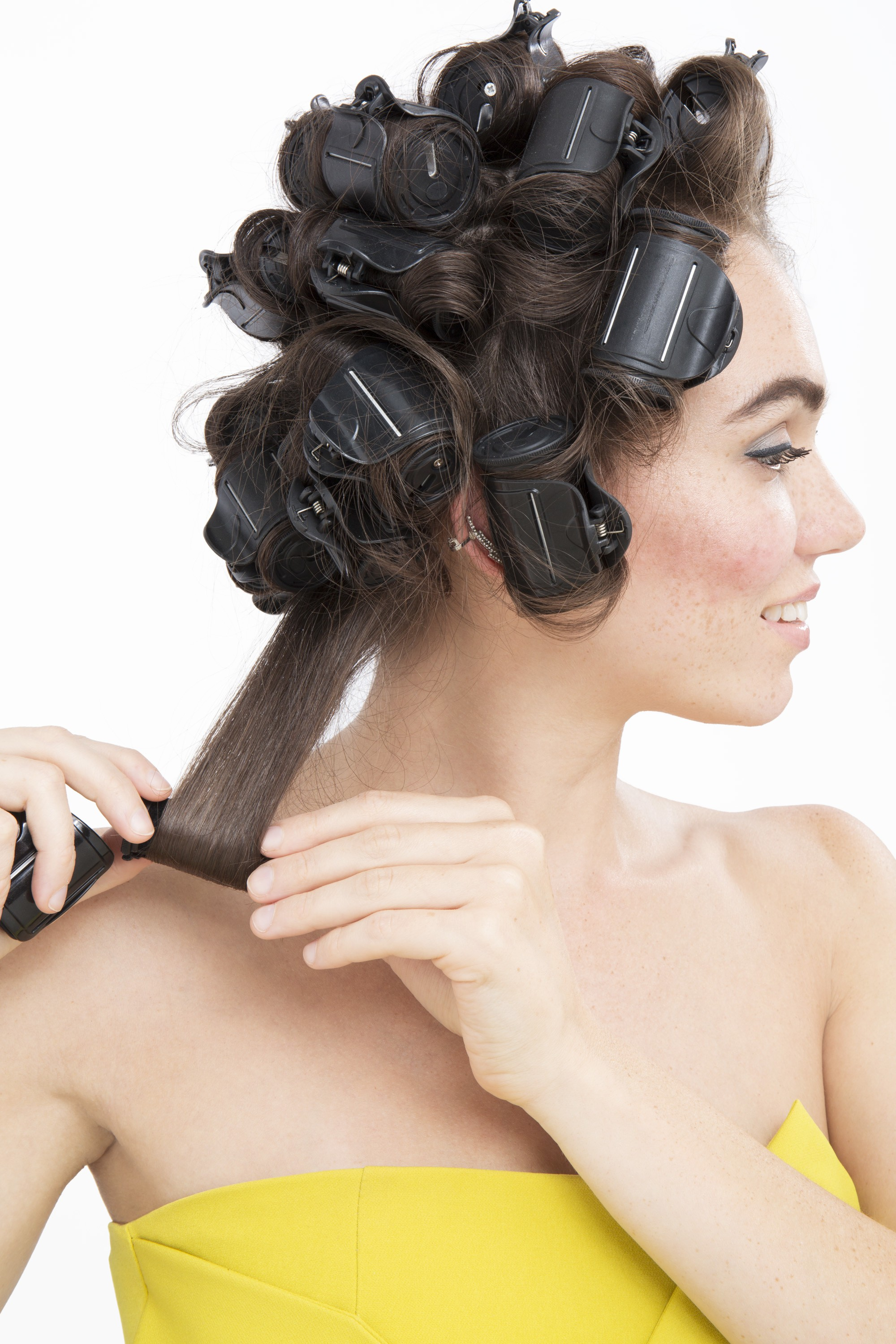 brunette model in strapless yellow dress with heated rollers in