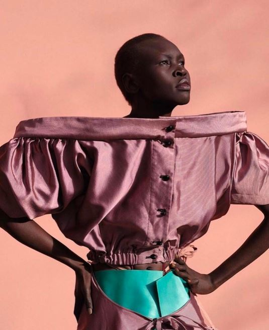 side view of alek wek with short buzzcut hair