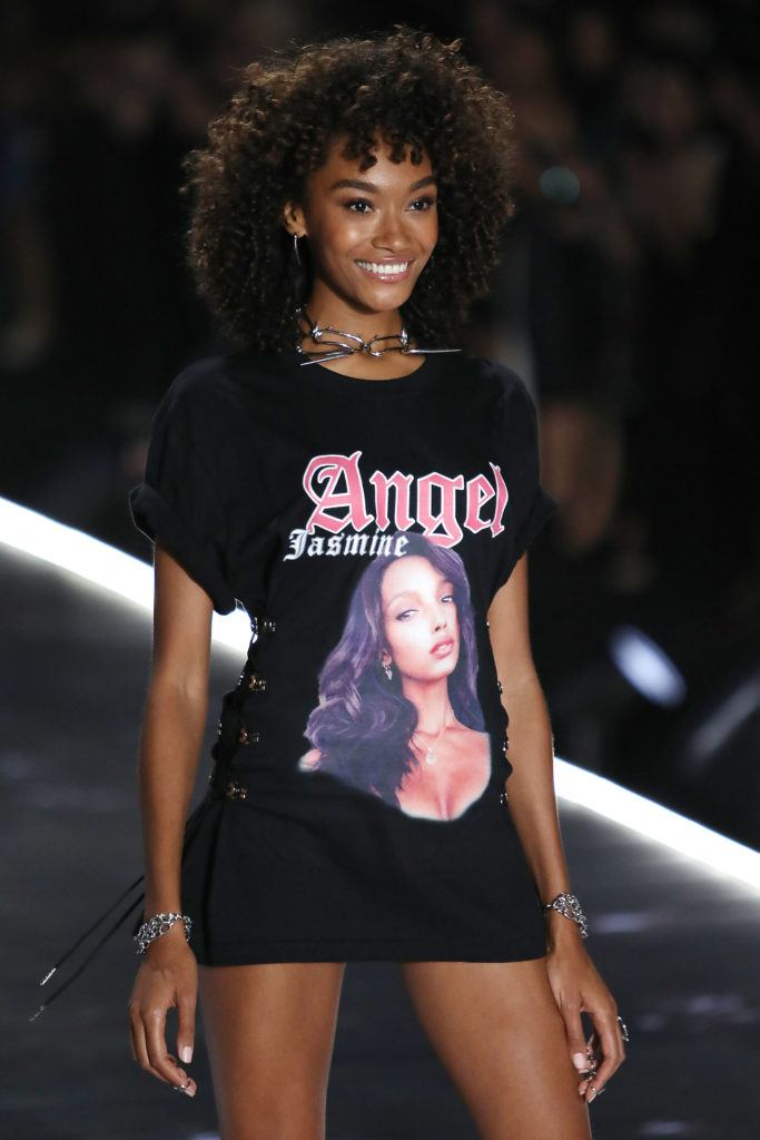 Victoria's Secret Fashion Show 2018: Cheyenne Maya Carty with medium curly shag hairstyle, wearing black top with angel slogan on it and posing on the runway