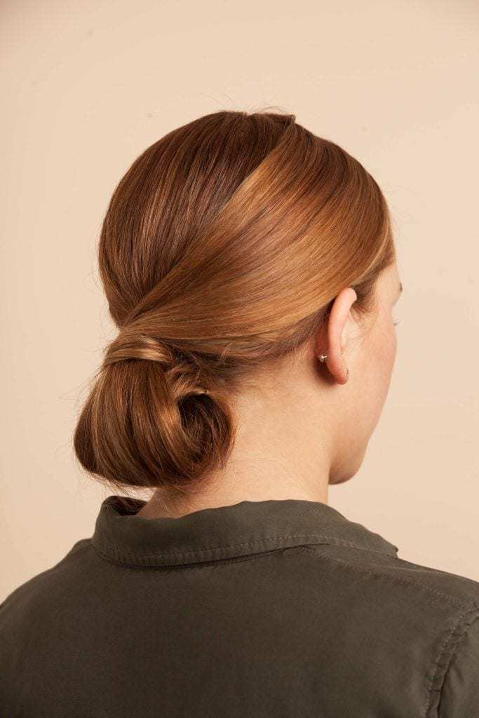 model with auburn hair in a curled under chignon updo
