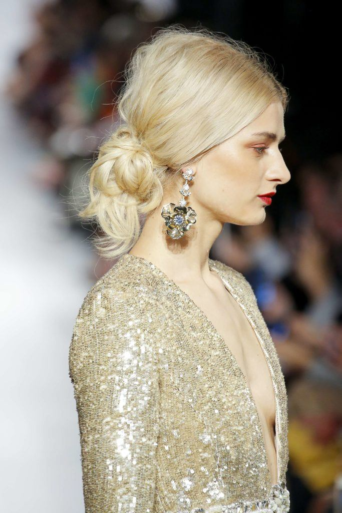 Christmas hairstyles: Blonde model with straight hair in low bun updo with volume at the crown. Model is wearing a glitzy gold dress and dangly earrings on runway.