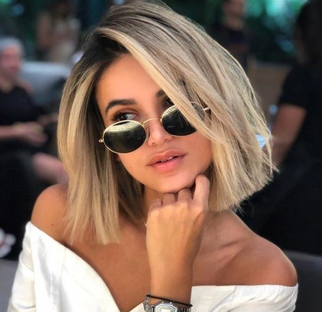 close up shot of woman with side swept ash blonde bob hairstyle, wearing black sunglasses and a white shirt, posing in a hair salon