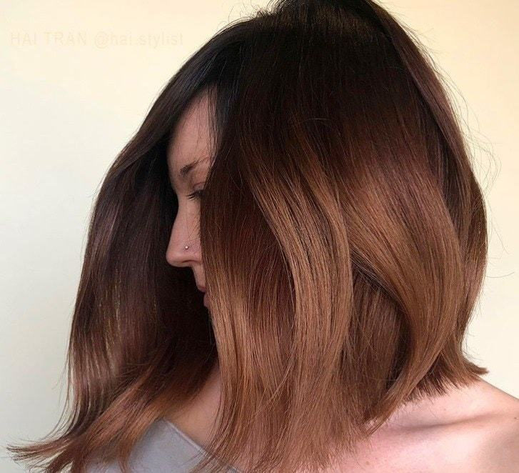 Cocoa cinnamon hair colour: Close up shot of a woman with wavy dark brown medium hairstyle with cinnamon ends.