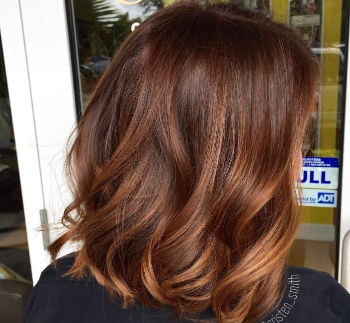 Cinnamon hair colour: Back shot of a woman with mid-length, wavy brown hair with cinnamon and pumpkin highlights.