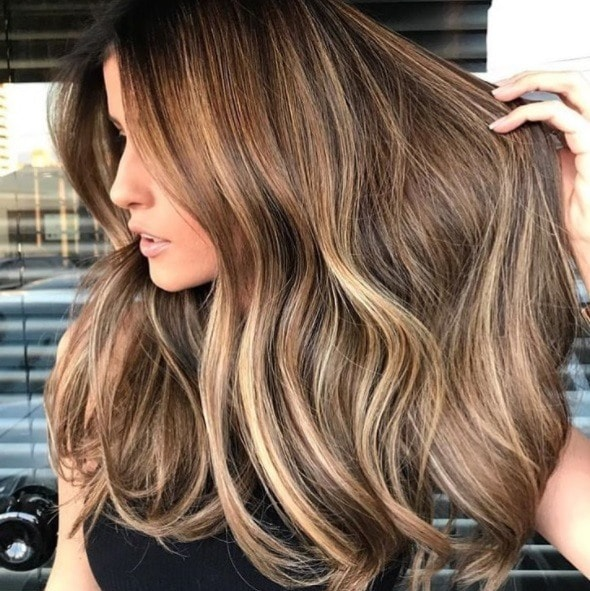 Cinnamon hair colour: Close up shot of a woman with long, light brown hair with cinnamon balayage.