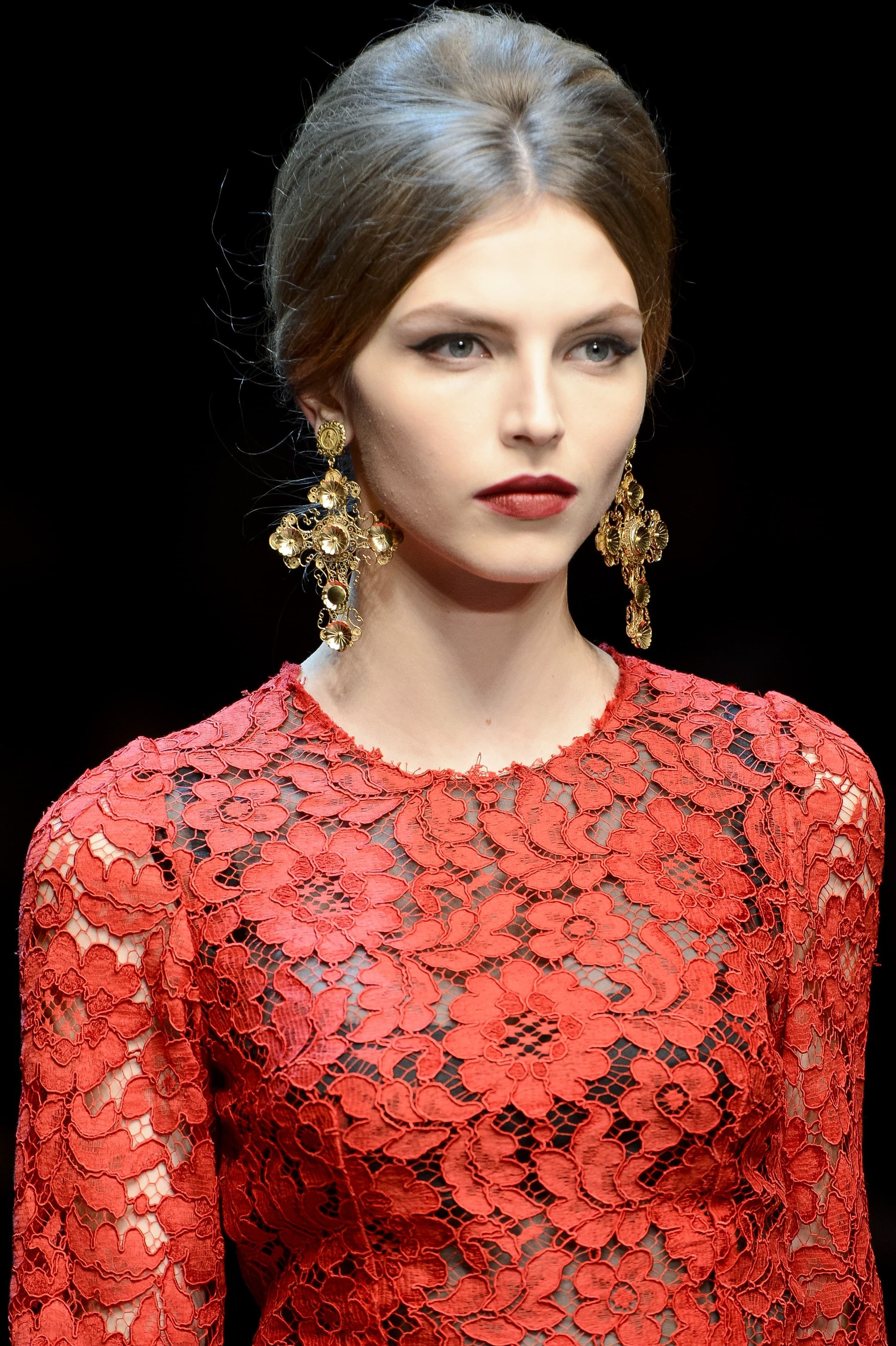 close up shot of model on the d and g runway with sleek mini bouffant hairstyle, wearing red dress and drop earrings