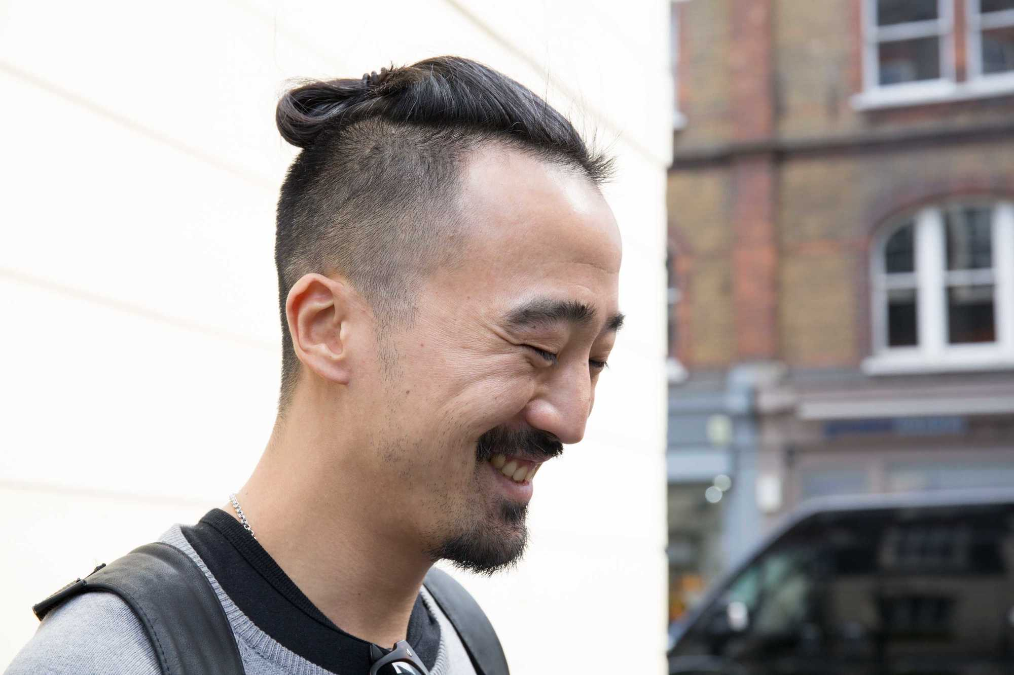 Man bun and beard: Close-up street style shot of a man with a bumped-up clipped man bun with shaved undercut and a goatee