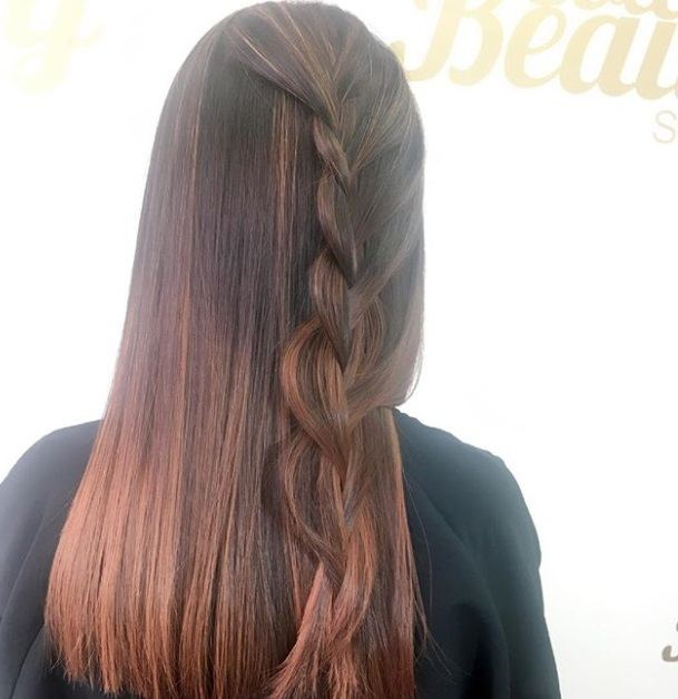 Cinnamon hair colour: Close up shot of a woman with dark brown hair with cinnamon highlights styled into a half-up, half-down braid.