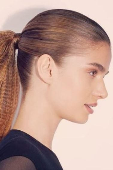 Crimped hair: Woman with dark blonde hair in ponytail with crimped ends wearing a black top.