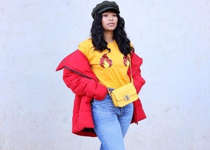 protective hairstyles for natural hair: close up shot of woman with red jacket, yellow top, wearing wig and baker boy hat