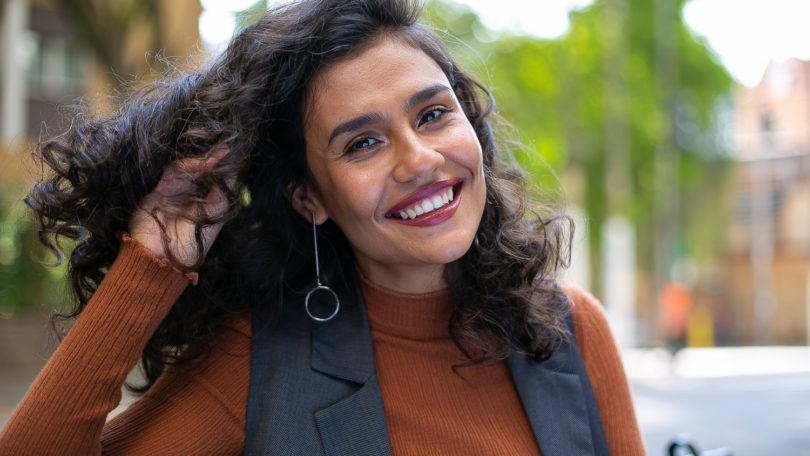 Best brush for curly hair guide: close up shot of woman with natural curly hair, wearing a brown top and grey jacket, wearing drop earrings and posing outside