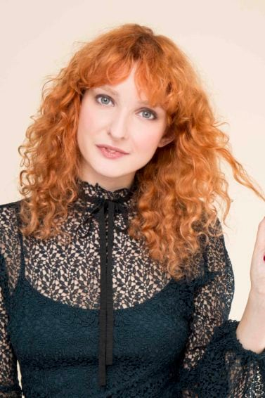 front view of red head model with full curls and fringe with strand of hair in her hand