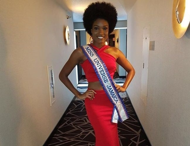 close up shot of davina bennet with natural afro hairstyle, wearing red jumpsuit and miss Jamaica sash