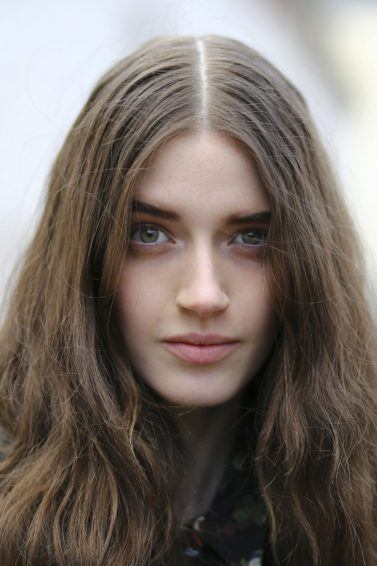 cream for dry hair guide: close up shot of woman with dry, wavy hair, posing for a streetstyle shot