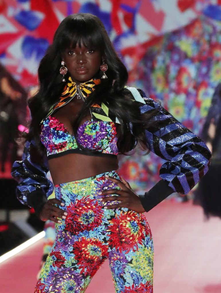 Victoria's Secret Fashion Show 2018: Duckie Thot with dark brown hair with wispy straight bangs and long waves, wearing floral pattern outfit on the runway