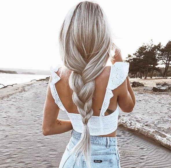 back shot of woman with ash blonde silver hair fashioned into a loose plait, wearing white crop top and jeans while posing on a beach