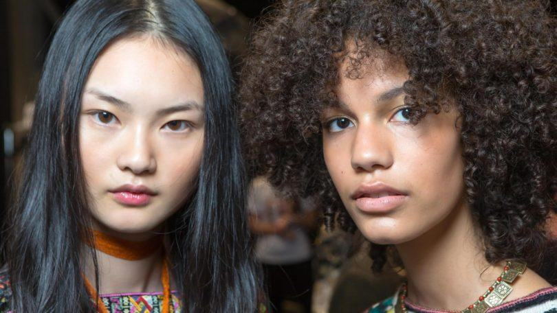 hair type quiz: close up shot of two models backstage with different hair types posing next to eachother