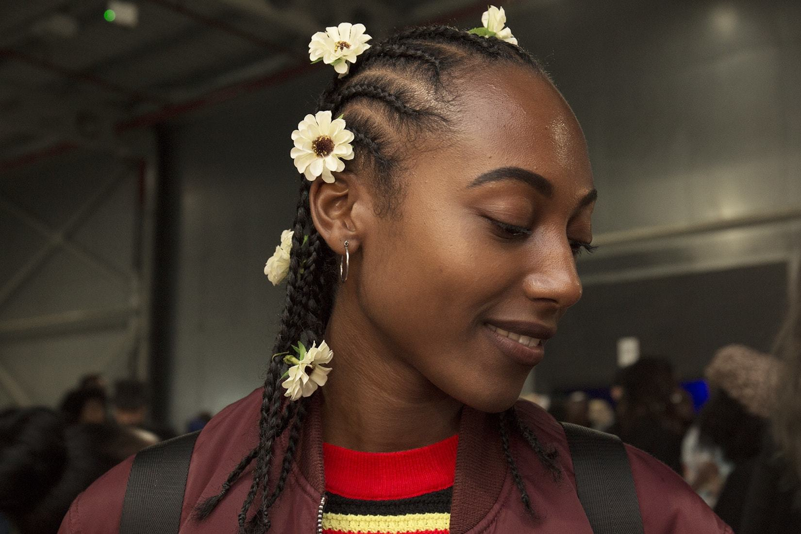 Low manipulation hairstyles: Close up shot of black girl with cornrow hairstyle that has flowers in it, posing at afropunk london festival