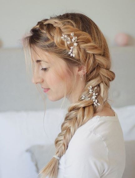 Fishtail braid: Woman with long blonde hair styled in a fishtail braid with baby's breathe flowers sitting in a white room.