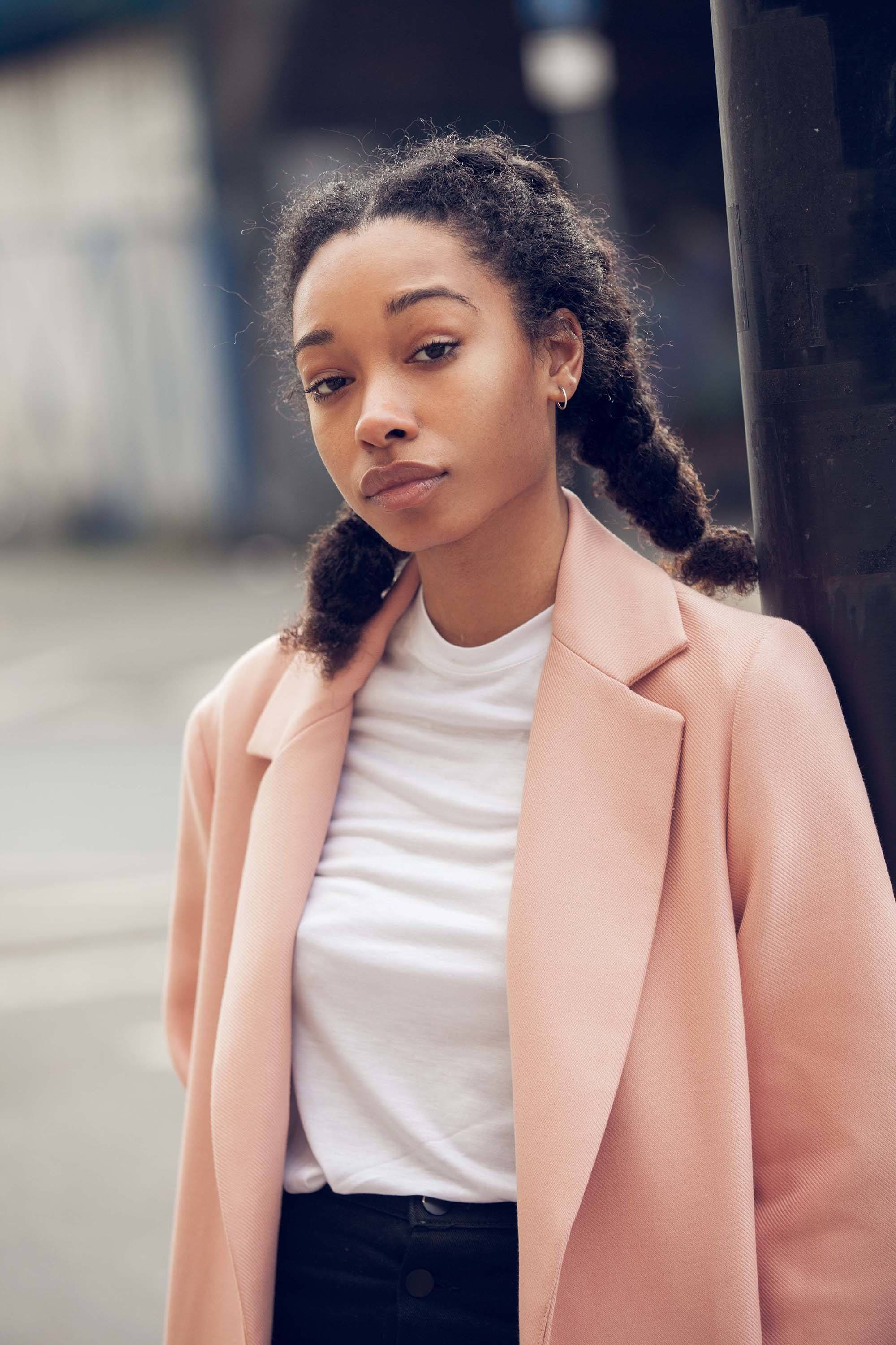 Low manipulation hairstyles: Close up of black model with pigtails hairstyle, wearing pink jacket and white shirt, street style