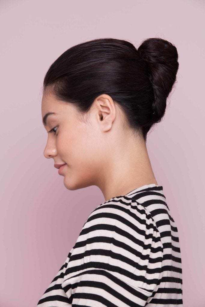 French twist on model with medium brown hair wearing a striped top