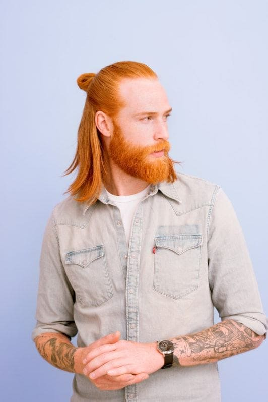 Man bun and beard: Ginger man with long hair in a half-up half-down man bun with a beard, wearing a denim shirt and posing against a lilac background