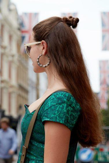 Easy Black Friday hairstyles: Woman with long chestnut brown hair styled into a half-up, half-down knot bun posing outside, wearing green