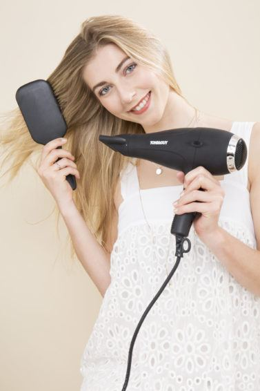 blonde model brushing her hair and drying it with a hairdryer