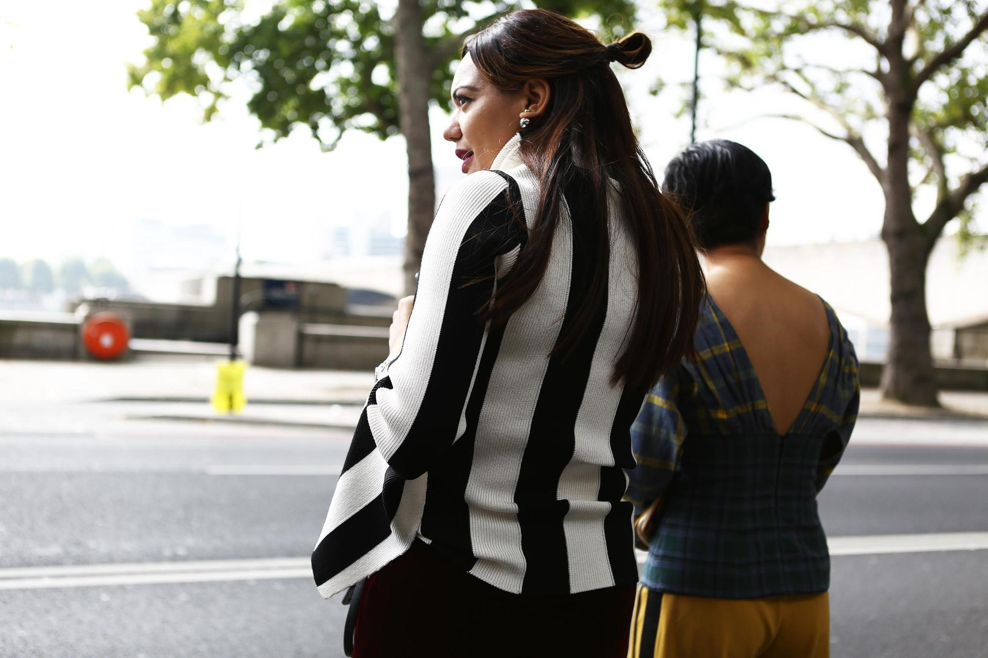 back side view of street style model with long dark hair in half-up, half-down bun