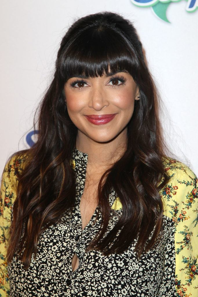 Ponytail and bangs: Hannah Simone with long dark brown wavy hair in half-up, half-down with full bangs.