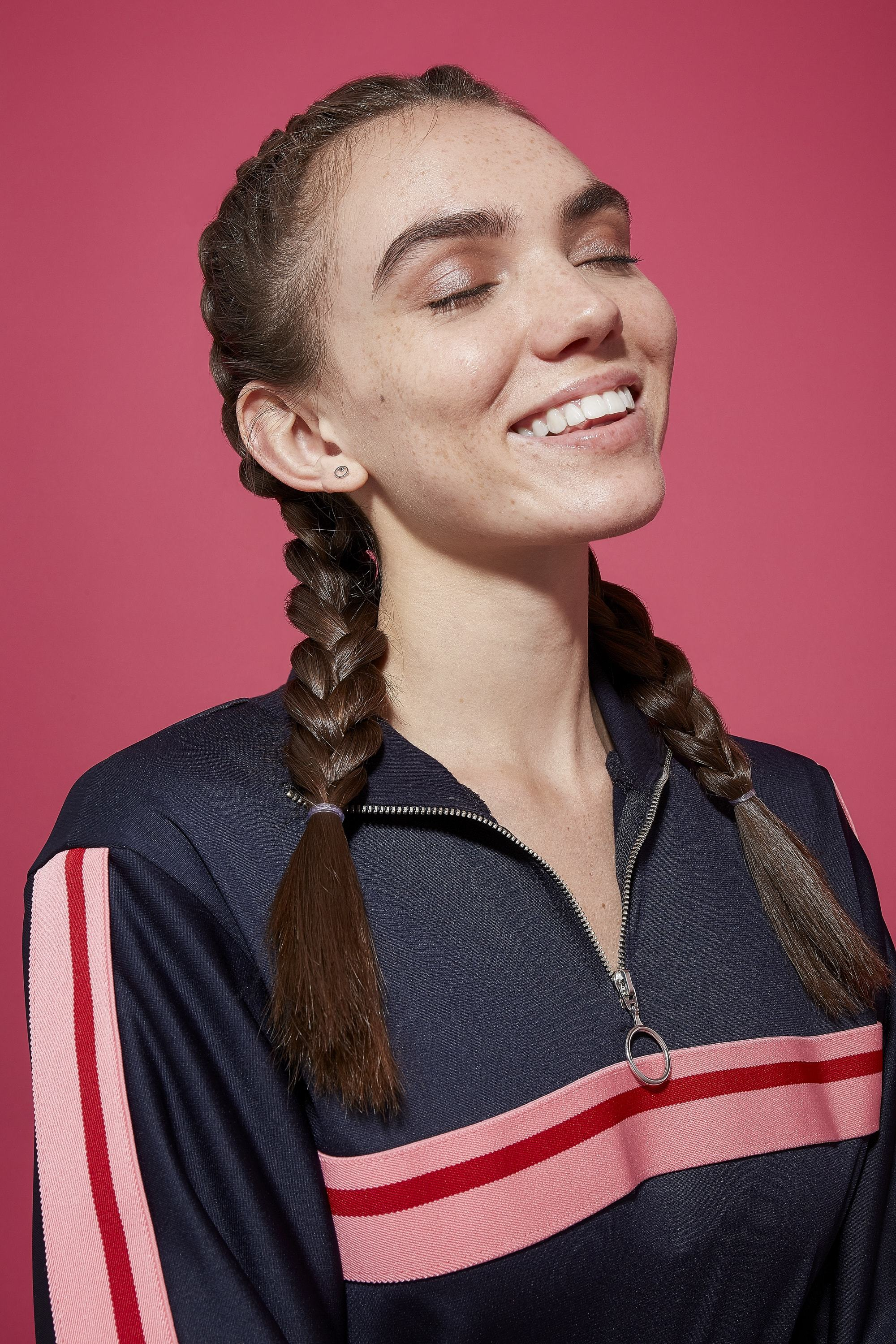 hair updos: brunette model with long hair styled in boxer braids in studio with dark pink background wearing sports top