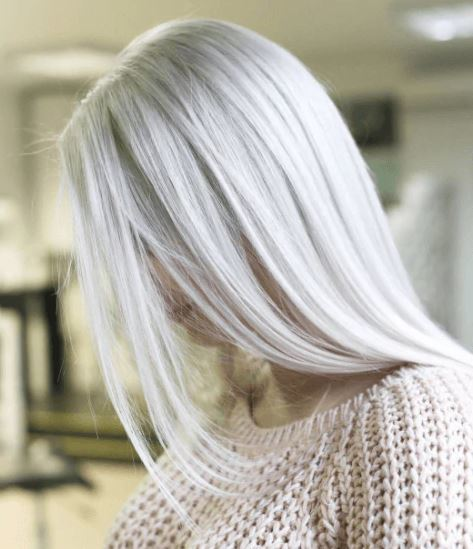 Shades of blonde hair: Woman with long straight ice blonde hair wearing a beige knitted jumper.